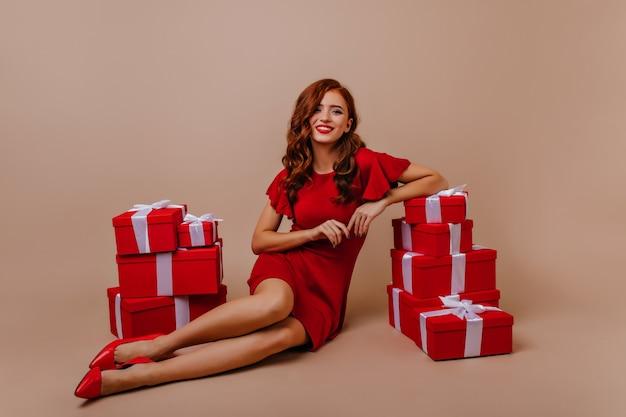 생일 파티에서 포즈 곱슬 헤어 스타일으로 흥분된 소녀. 새 해 옆에 앉아 빨간 드레스에 화려한 여자를 제공합니다. 무료 사진