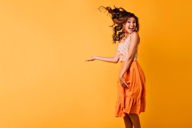 黄色にジャンプする生姜ウェーブのかかった髪の興奮した女の子。笑顔で踊るオレンジ色の服装で至福の若い女性のスタジオポートレート。 無料写真
