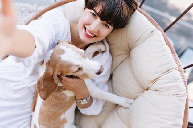 Ragazza emozionante con capelli castani corti che ride mentre prende la foto di se stessa con il cane beagle. Foto Gratuite