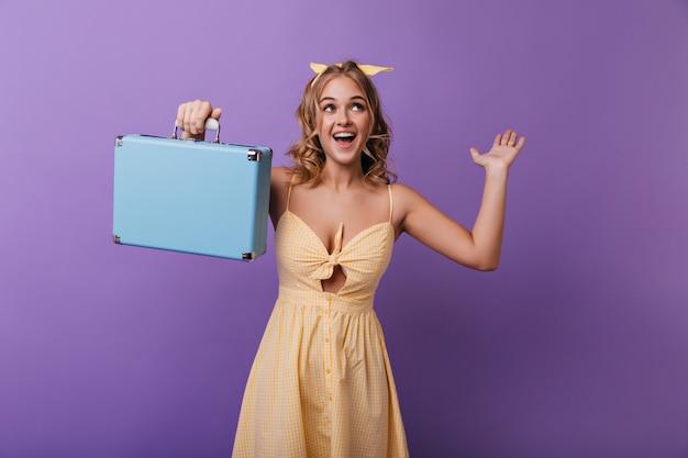 彼女の旅行スーツケースを保持している日焼けした肌を持つ興奮した女の子。ポジティブな感情を表現するスーツケースで幸せな女を笑う。 無料写真