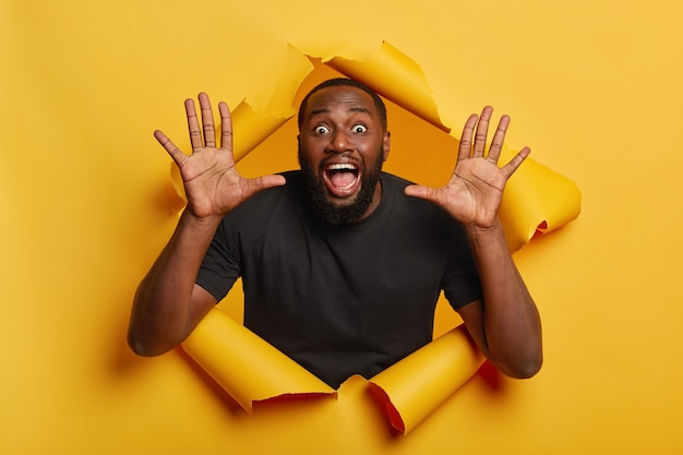 Il ragazzo dalla pelle scura, molto sorpreso, tiene la bocca e gli occhi ben aperti, alza i palmi delle mani, indossa una maglietta nera, si trova su un muro di carta gialla strappata. concetto di emozioni. Foto Gratuite