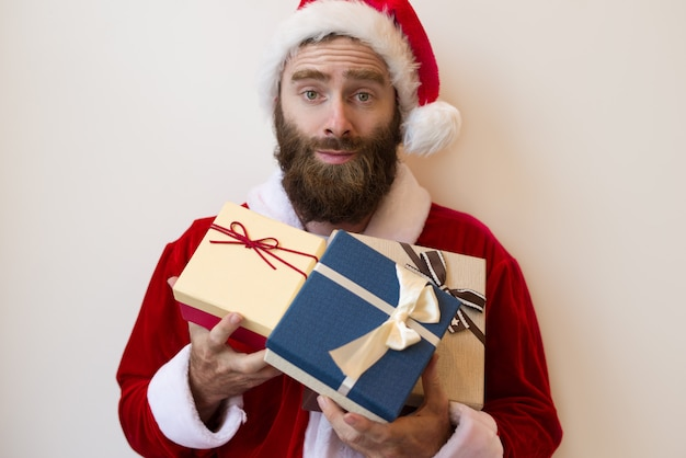 Excited guy wearing santa costume and holding gift boxes Free Photo