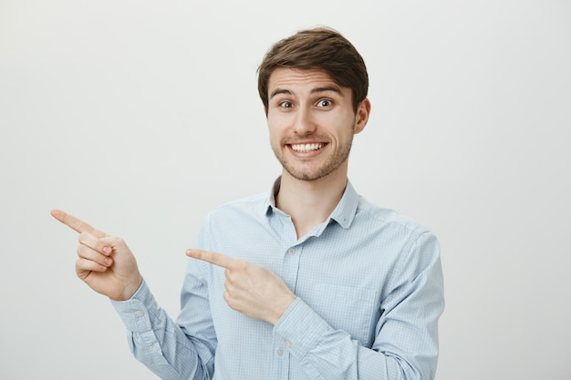Excited handsome man smiling broadly, pointing fingers left at promo banner Free Photo