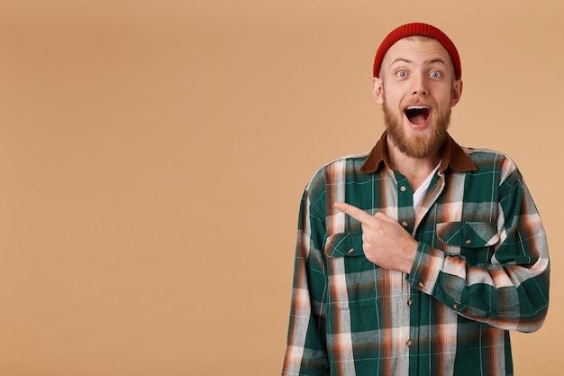 Il maschio emotivo barbuto felice eccitato in cappello rosso ha sorpreso l'espressione facciale, punti con il dito indice nell'angolo sinistro Foto Gratuite