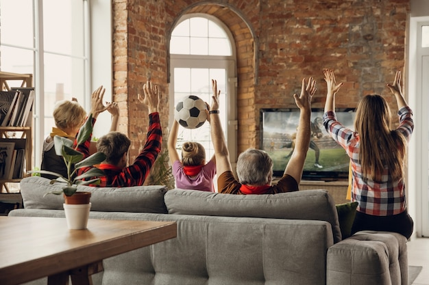Excited, happy big family team watch sport match together on the couch at home Free Photo