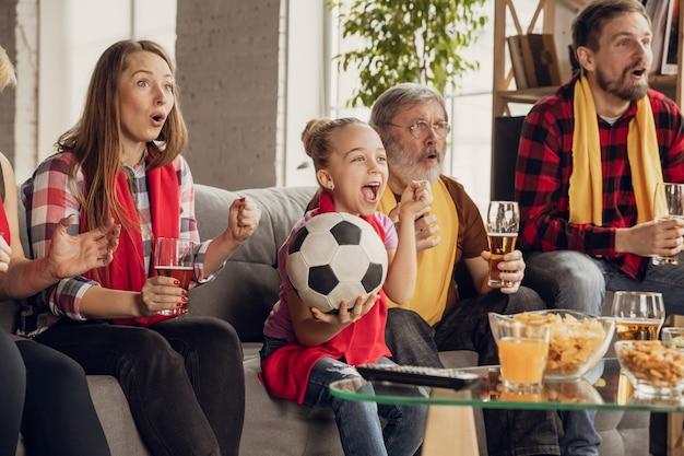 自宅のソファでサッカー、サッカーの試合を見ている興奮した、幸せな大家族。好きな代表チームを応援するファン。祖父母から子供まで楽しんでいます。スポーツ、テレビ、チャンピオンシップ。 無料写真