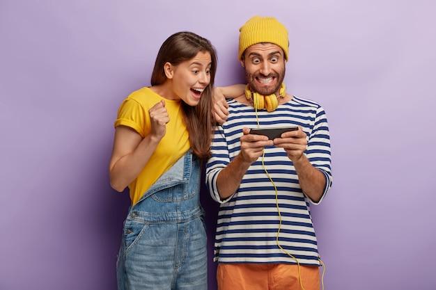 La coppia felice eccitata utilizza il telefono cellulare per giocare ai giochi online, guarda in modo impressionante il dispositivo smartphone, è ossessionata dalle tecnologie moderne, vestita con abiti alla moda. dipendenza da internet Foto Gratuite