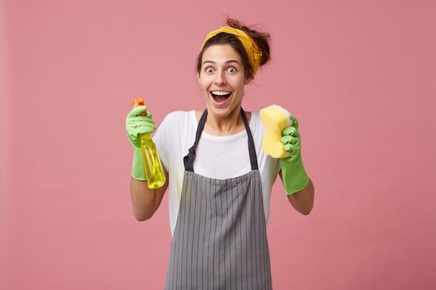 Взволнованная счастливая домохозяйка в желтом шарфе на голове и фартуке держит спрей с губкой, глядя с широко открытыми глазами и ртом Бесплатные Фотографии