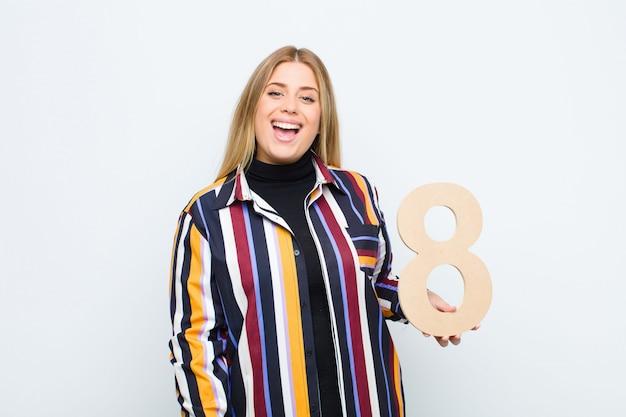 Взволнован, счастлив, радостен, держит номер 8. Premium Фотографии