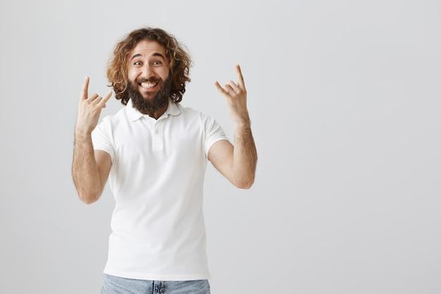 Uomo del medio oriente emozionante e felice che mostra il gesto del rock-n-roll, divertendosi Foto Gratuite
