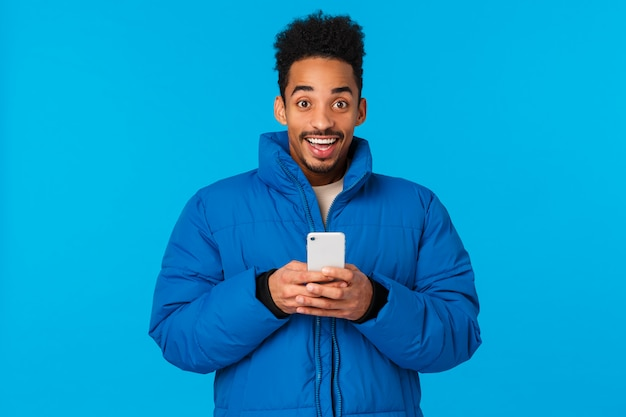 Excited happy smiling african american in padded winter jacket, holding smartphone and grinning upbeat, receive invitation party, chatting friends, got famous on social media, blue Premium Photo