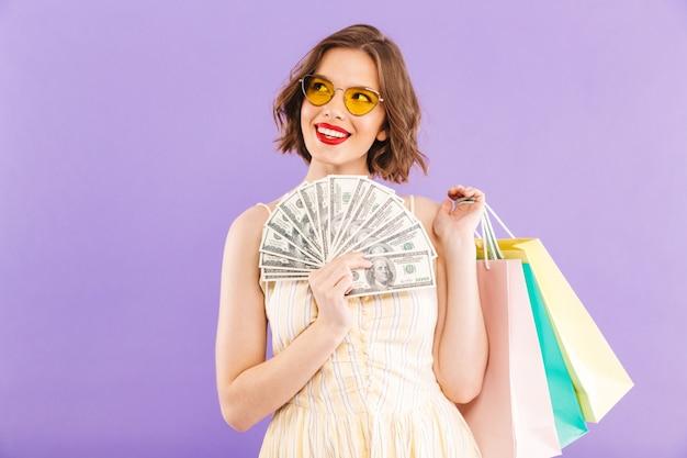 쇼핑백과 돈을 들고 고립 된 행복 한 여자를 흥분. 프리미엄 사진