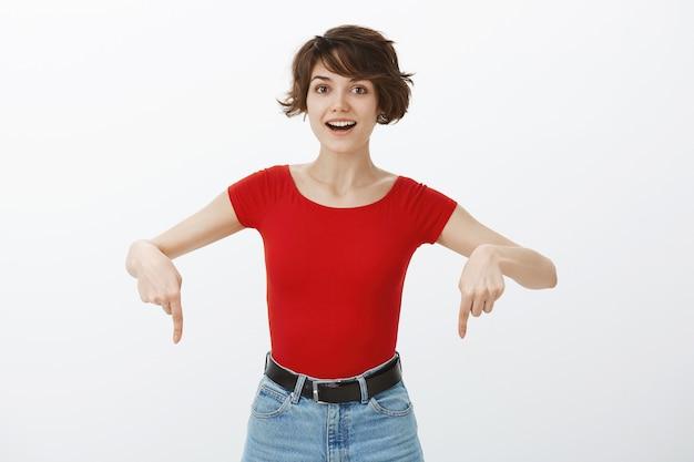 놀란 찾고 손가락 아래로 가리키는 흥분된 행복 한 여자 무료 사진