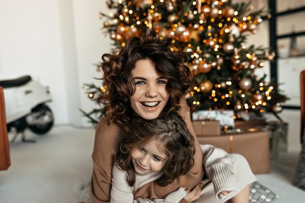 クリスマスを祝いながら笑って楽しんでいる小さな娘と興奮した幸せな女性 無料写真