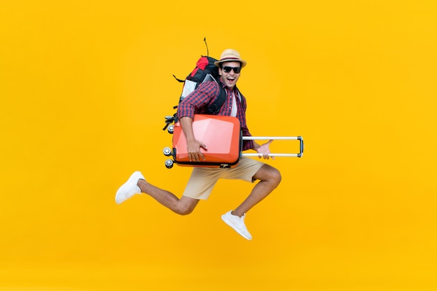 Excited happy young asian man tourist with luggage jumping Premium Photo