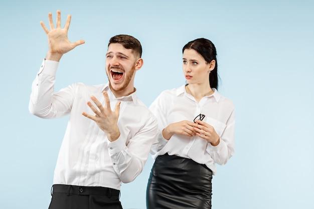 Giovani coppie felici emozionanti che esaminano macchina fotografica con gioia. uomo d'affari e donna isolata su sfondo blu studio Foto Gratuite