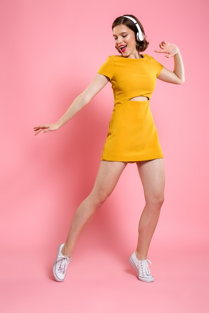 Excited happy young lady in yellow dress dancing Free Photo