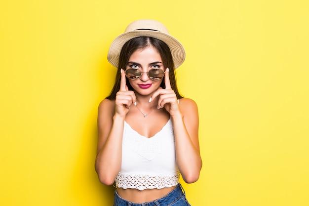 帽子と黄色の壁にサングラスで興奮している内気な少女 無料写真