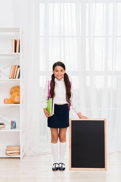 Excited hispanic schoolgirl with copybooks and chalkboard Free Photo