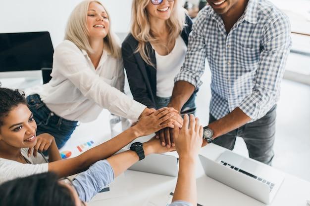 Взволнованные иностранные студенты в повседневной одежде готовы к командной работе. крытый портрет радостной девушки-мулата с вьющимися волосами, держащей руки с европейской леди и африканским молодым человеком в офисе. Бесплатные Фотографии