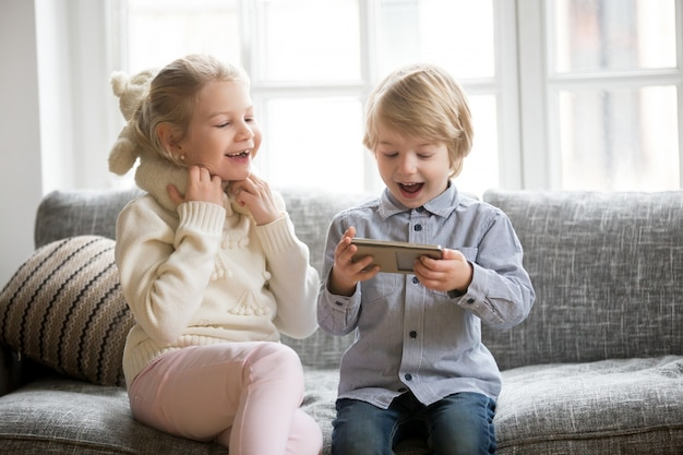 Excited kids having fun using smartphone sitting together on sofa Free Photo