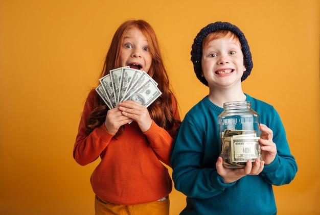 Excited little redhead children holding money. Free Photo