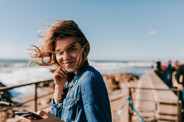Excited lovable model enjoying outdoor photoshoot with smile happy woman listening music on the shore of ocean and posing Free Photo