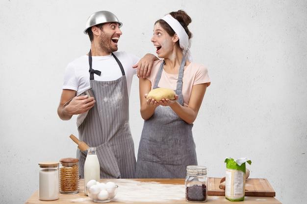 興奮した男性と女性の料理人は成功を喜び、笑顔でお互いを見つめ、表現を大喜びしています 無料写真