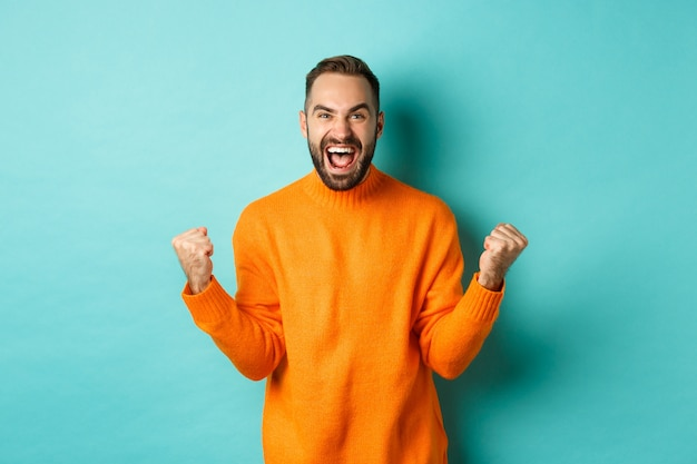 Excited man celebrating victory, rejoicing and making fist pump gesture, winning and looking satisfied, saying yes, achieve goal, standing over light turquoise wall. Free Photo