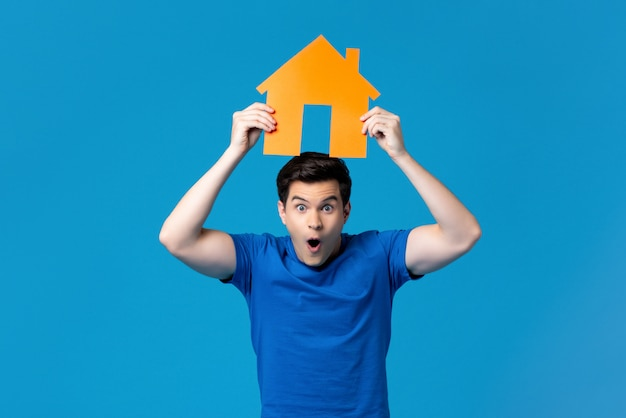 Excited man holding a housing model overhead Premium Photo