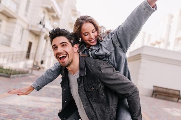 ガールフレンドと一緒に身も凍るような黒のデニムジャケットを着た興奮した男。街を探索する幸せなカップルの屋外の肖像画。 無料写真