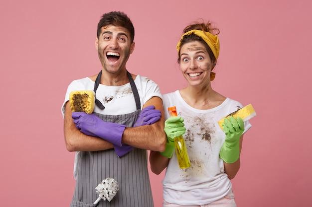 手を繋いでいるカジュアルな服装で興奮している男は、彼の仕事を喜んで汚れたスポンジを持って交差しました。黄色のヘッドバンドと洗剤とスポンジを洗う窓を保持している白いtシャツを着て笑顔の女性 無料写真