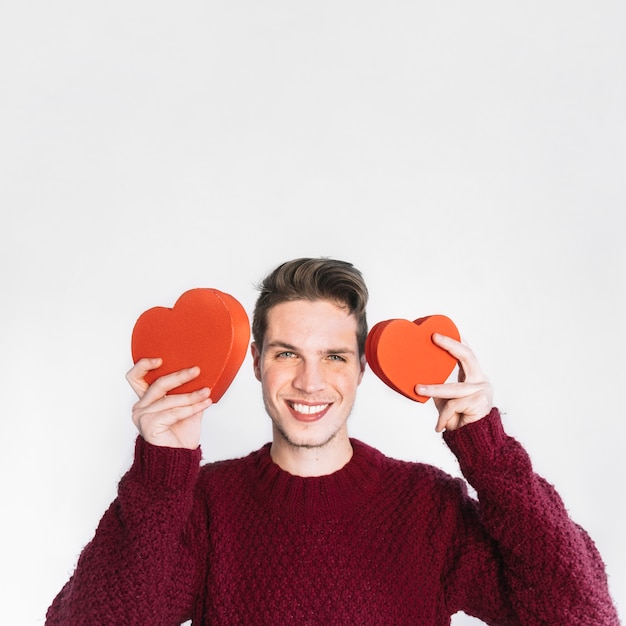 Excited man in love posing with hearts Free Photo