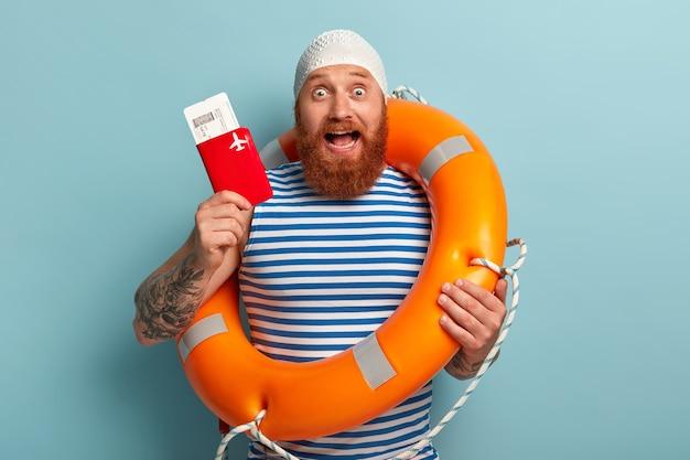 興奮した男は、パスポート付きの搭乗券の飛行を示し、オレンジ色の救命浮輪を運び、海外旅行の準備をします 無料写真