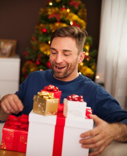 크리스마스 선물의 스택과 함께 흥분된 남자 무료 사진
