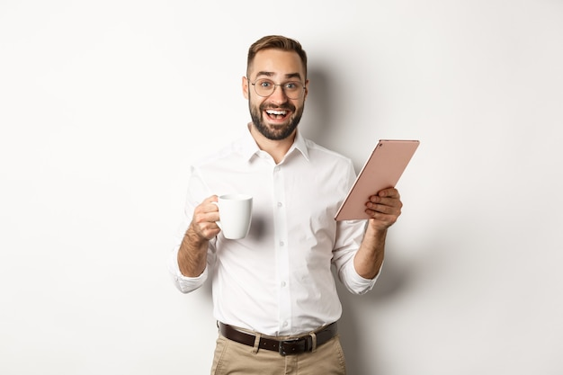 Responsabile eccitato che legge sulla tavoletta digitale, lavora e beve caffè, in piedi Foto Gratuite