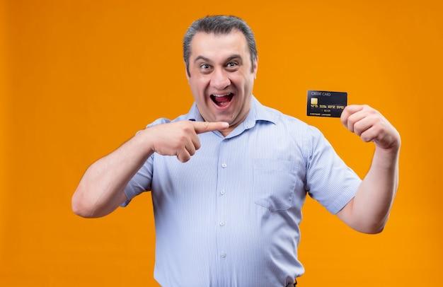 Eccitato uomo di mezza età che indossa la camicia spogliata verticale blu punta con la carta di credito del dito indice tenendo la bocca aperta Foto Gratuite