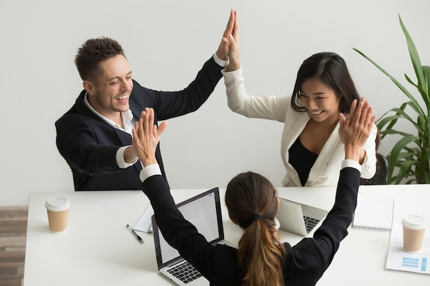 Excited multiracial team holding hands giving high five celebrating success Free Photo
