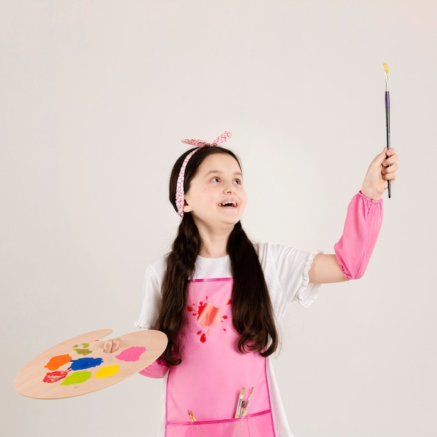 Excited painter holding paint brush Free Photo