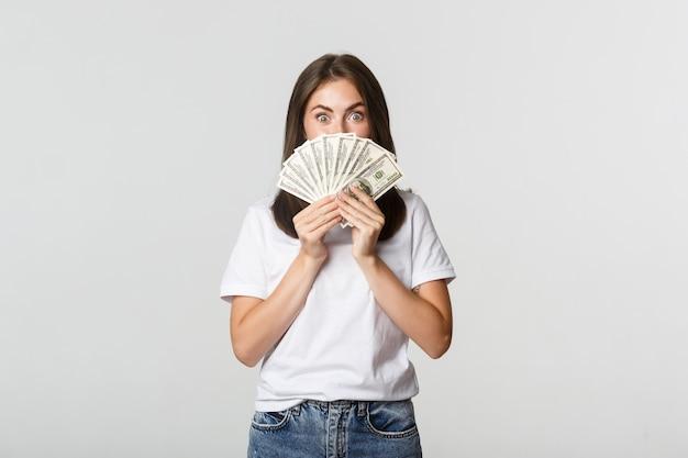 白く立って、顔にお金を持っている興奮したかなり若い女性。 無料写真