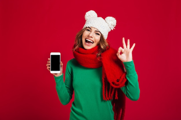 Excited pretty young woman showing display of phone Free Photo