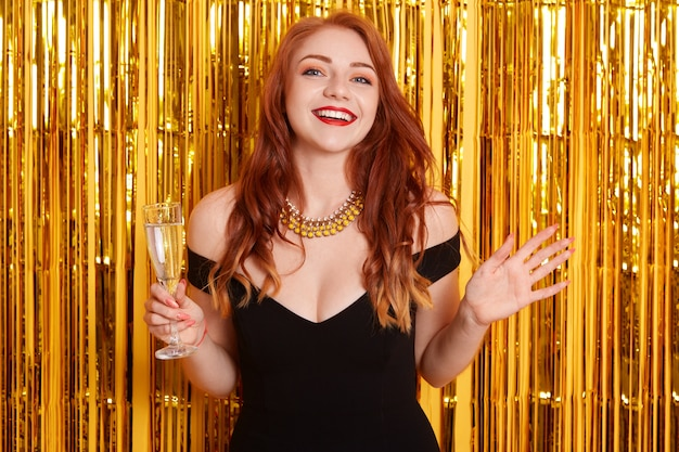 Excited red haired female with spreading hands aside, holding glass of wine, celebrating new year, standing against yellow wall with golden glitter. Free Photo
