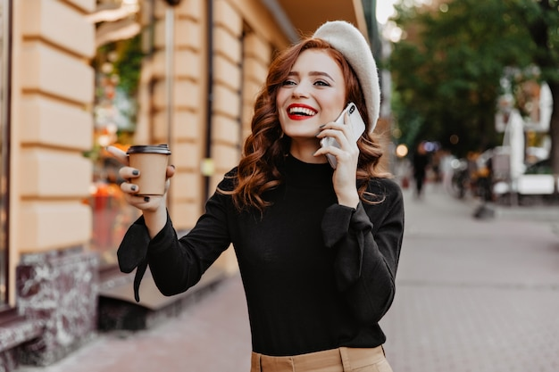 Excited red-haired girl drinking coffee on the street. appealing stylish woman talking on phone on city wall. Free Photo