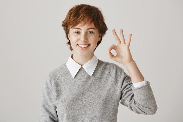 Ragazza rossa eccitata e soddisfatta con taglio di capelli corto in posa contro il muro bianco Foto Gratuite