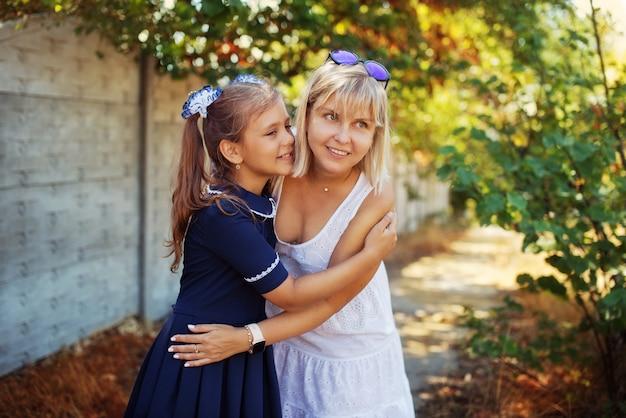 興奮した女子高生がお母さんを抱きしめる Premium写真