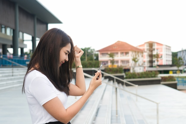 Excited screaming young asian woman student reading good news on mobile phone. Premium Photo