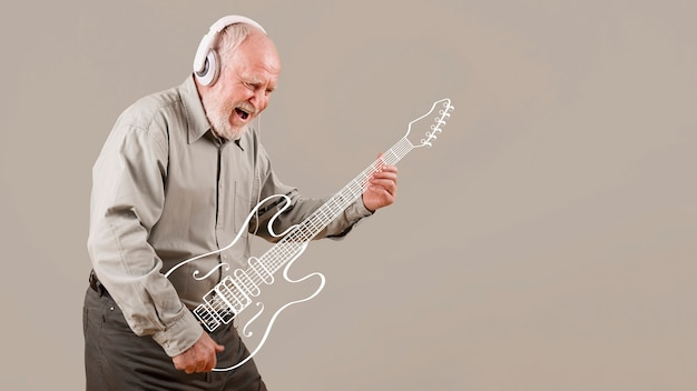 Excited senior playing imaginary guitar Premium Photo
