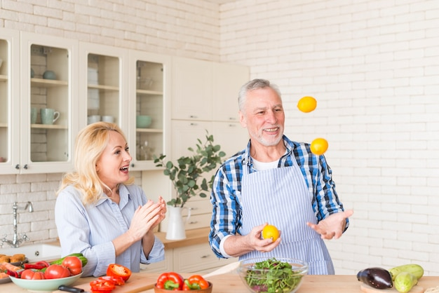 Excited senior woman clapping while her husband juggling lemons in the kitchen Free Photo