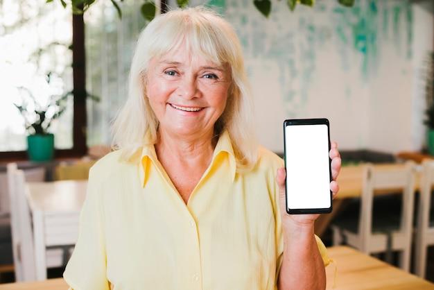 Excited усмехаясь пожилая женщина показывая smartphone к камере Бесплатные Фотографии