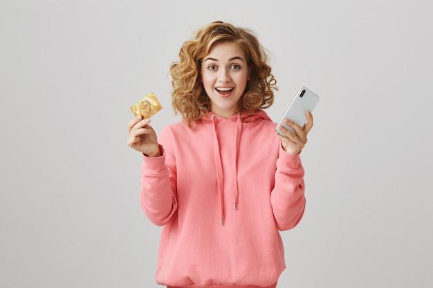 Взволнованная улыбающаяся кудрявая девушка показывает кредитную карту, оплачивая онлайн-заказ с помощью смартфона Бесплатные Фотографии